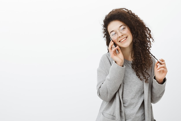 Waist-up shot of outgoing friendly stylish girl with curly hair in stylish eyewear and grey coat, talking on smartphone, tilting head and smiling broadly