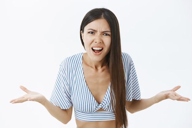 Mezzo busto di donna asiatica confusa arrabbiata e arrabbiata che scrolla le spalle con i palmi sparsi Foto Gratuite