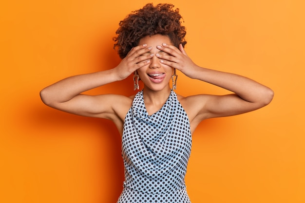 Waist up shot of playful woman covers eyes hides face sticks out tongue wears star shaped earrings and polka dot shirt isolated over orange wall