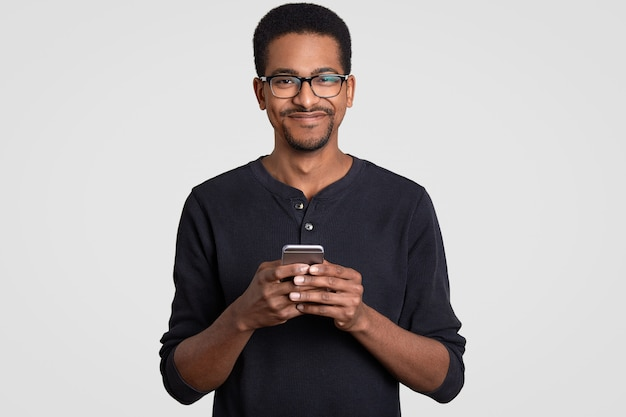 Waist up shot of pleased cheerful dark skinned young man holds smart phone in hands, types message, makes online shopping
