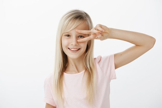Waist-up shot of positive charming child with blond hair in casual outfit, showing victory or peace gesture over eye and smiling happily, dancing or having fun over gray wall, being in great mood