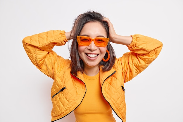 Waist up shot of positive fashionable asian millennial girl has dark hair keeps hands on head smiles broadly wears trendy sunglasses jacket isolated over white wall being in good mood.