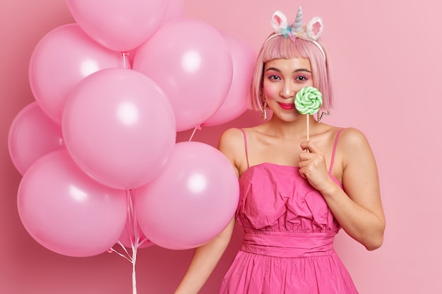 Waist up shot of pretty pleased asian woman holds sweet lollipop smiles pleasantly has brightmakeup and dress holds inflated balloons prepares for celebration or party isolated over pink background.