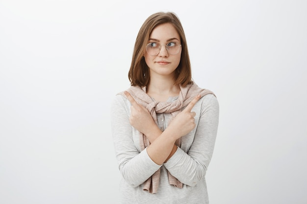 Waist-up shot of relaxed good-looking feminine girl in glasses with short brown hair crossing arms on body pointing in different sides left and right making choice or decision over gray wall