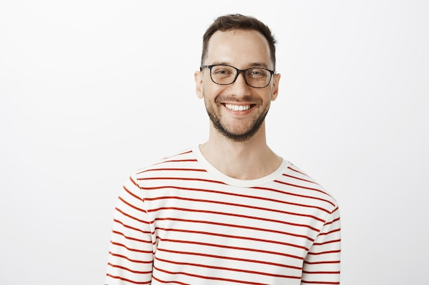 Waist-up shot of relaxed good-looking positive guy in glasses, smiling broadly