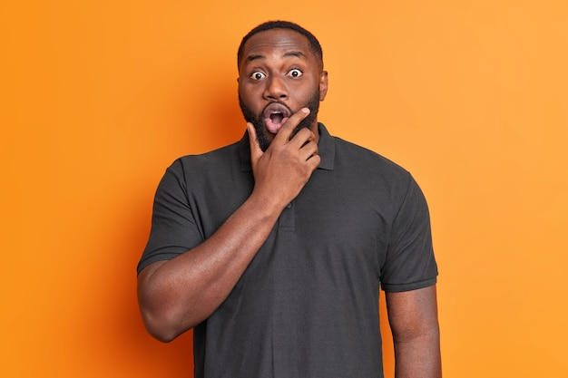 Waist up shot of scared shocked man holds chin and stares bugged eyes at front dressed in black t shirt surprised by something poses against bright orange wall