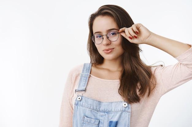 Mezzo busto di bella studentessa sensuale e civettuola con capelli castani toccando la montatura di occhiali pieghevoli labbra carine rendendo gli sguardi romantici davanti in piedi seducente sul muro grigio.