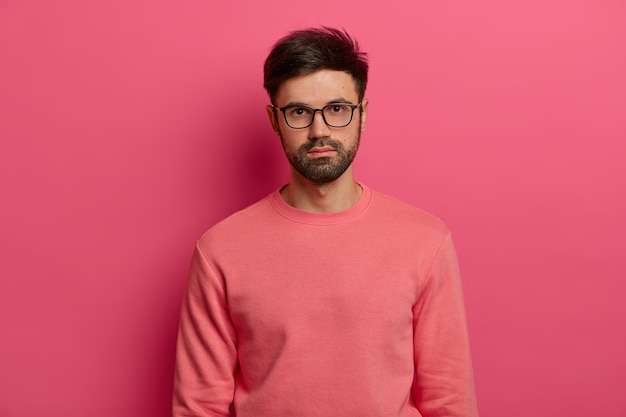 Waist up shot of serious male manager or freelancer looks  with calm expression, focused somewhere, comes on job interview, wears transparent glasses and sweater, poses over rosy wall