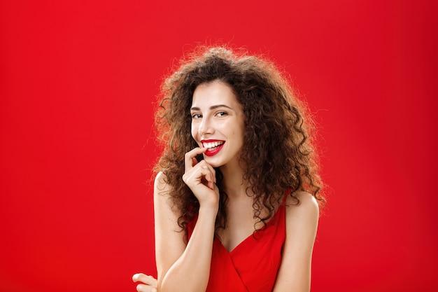 Mezzo busto di ragazza adulta sexy e sensuale con capelli ricci in vestito elegante che morde il dito e sorridente civettuolo seducente ragazzo caldo durante l'evento formale in posa romanticamente su sfondo rosso.