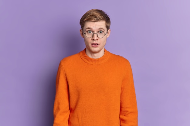 Waist up shot of shocked european man keeps mouth opened holds breath from amazement hears incredible news wears round spectacles and orange jumper