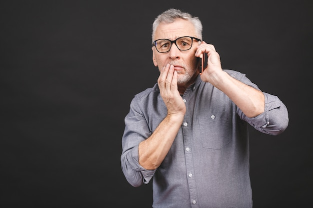 Waist-up shot of shocked senior man with glasses, worry and surprise holding smartphone receiving bad news looking concerned and stunned