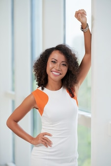 Waist-up shot of slender smiling woman posing at the window