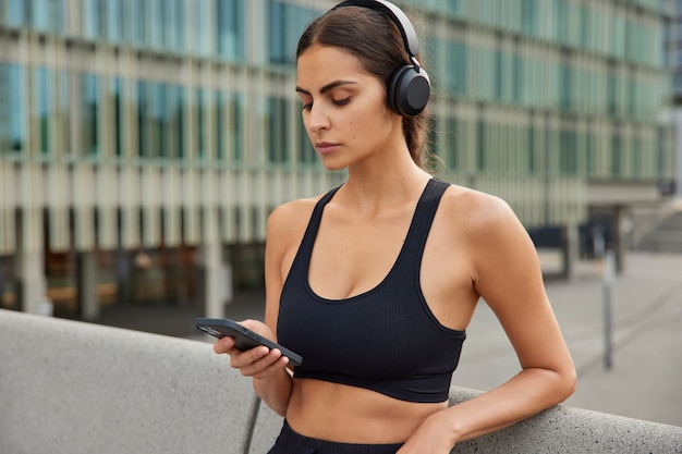 Waist up shot of sporty motivated female model downloads app for sport listens favorite music types on phone dressed in tank top uses yoga application poses in centre of city