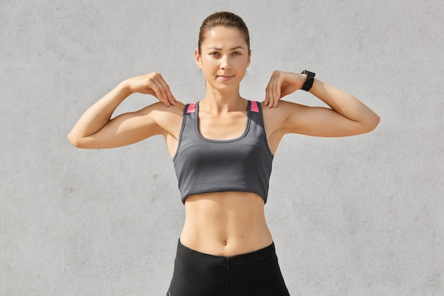 Waist up shot of sporty woman keeps both hands on shoulders, does exercises during morning workout, wears casual top and leggings