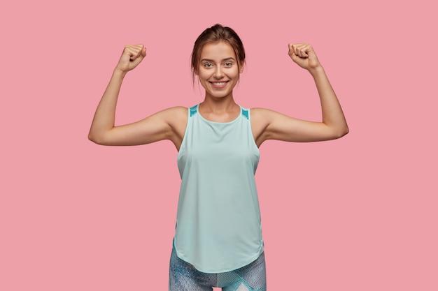 Mezzo busto di donna sportiva alza la mano per mostrare i suoi muscoli