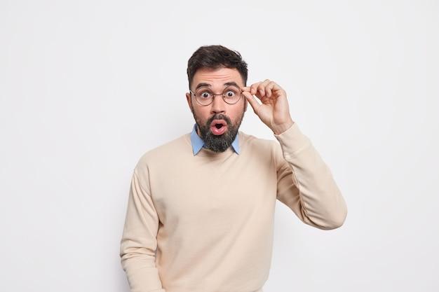 Mezzo busto sorpreso uomo barbuto scioccato tiene la mano sul bordo degli occhiali controlla qualcosa di sorprendente tiene la bocca aperta dallo stupore vestito con un maglione casual
