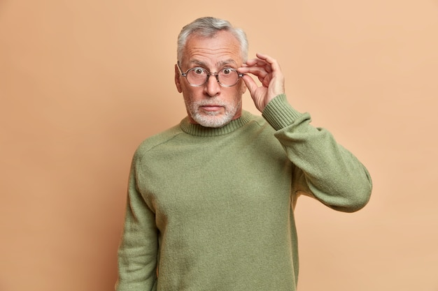Waist up shot of stunned senior man stares through glasses reacts on unexpected news gets shocked poses disturbed against beige wall wears casual clothes