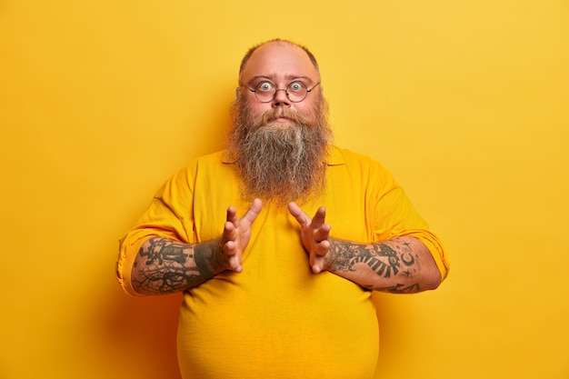 Waist up shot of surprised plump man has big belly, stares with bugged eyes, raises hands, afraids of something, dressed in casual t shirt, isolated on yellow wall. overweight surprised guy