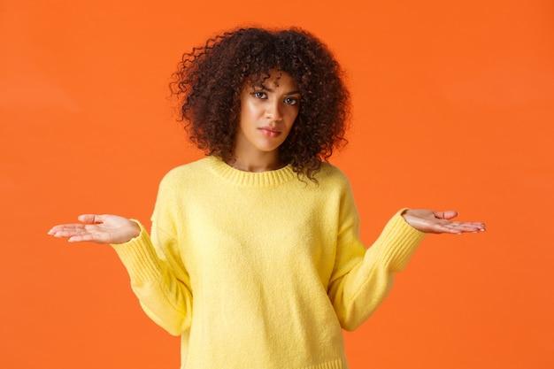 上半身ショットの動揺と欲求不満、無知なアフリカ系アメリカ人の縮毛の少女、手で肩をすくめ、横向きに横になって、うろたえ、わからない、理解できない、困惑した、オレンジ色の壁