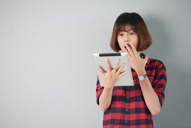 Waist up shot of woman looking at shocking content on her tablet pc