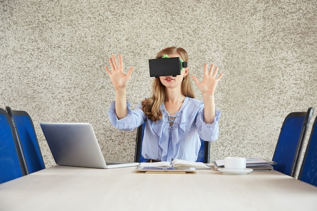 Waist up shot of woman wearing vr headset gesturing at the office desk