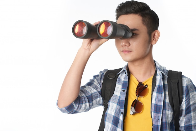 Waist-up shot of young guy looking through the binocular glass