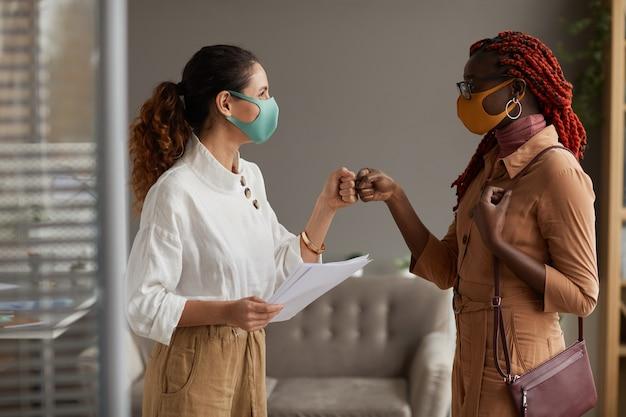 オフィスで非接触型の挨拶としてマスクとぶつかる拳を身に着けている2人の陽気なビジネスウーマンで上向きの側面図