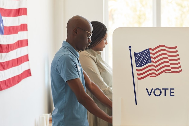 Waist up side view portrait of young african-american people standing in voting booth decorated with usa flags, copy space