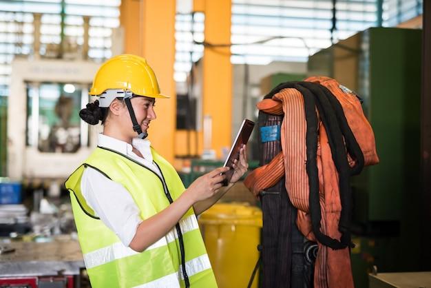 웃고 있는 여성 노동자가 공장 창고에 있는 태블릿에 있는 회사 응용 프로그램으로 생산 하드웨어 재고를 확인합니다. 재고 개념이 있는 산업.