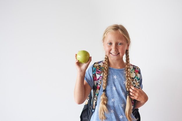 Waist up of student girl holding an apple