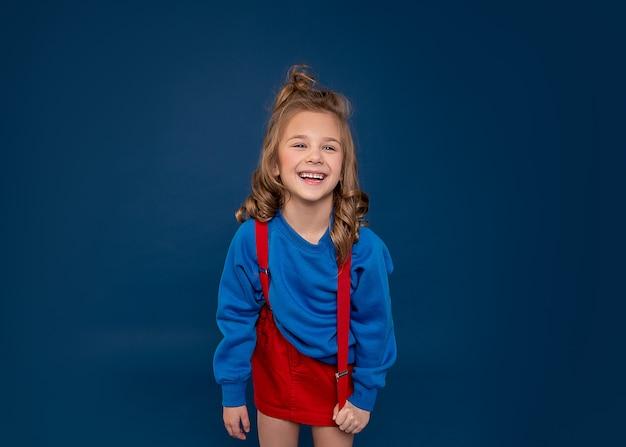 Талия вверх студийный портрет очаровательной детской девочки 6-7 лет смеясь от волнения, студия выстрелил на синем backgroud. концепция человеческих эмоций и мимики.