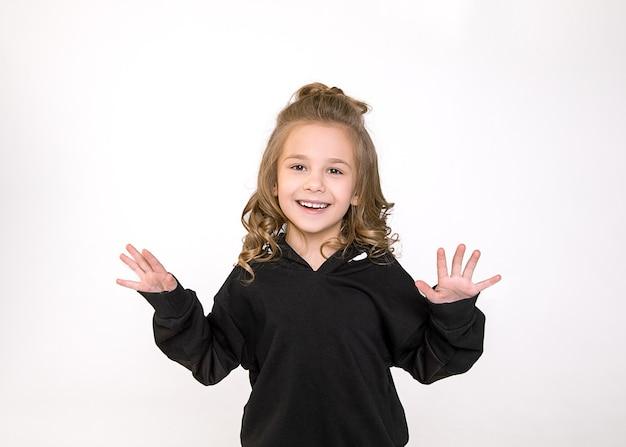 Талия вверх студийный портрет очаровательной детской девочки 6-7 лет смеясь от волнения, студия выстрелил на белом backgroud. человеческие эмоции, концепция мимики.