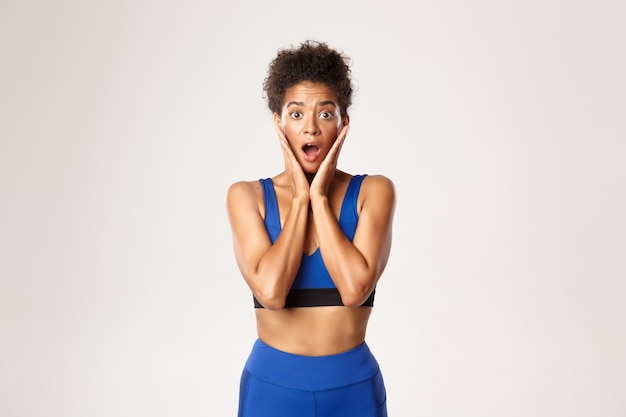 Waist-up of surprised african-american fit female athelte, looking amazed, open mouth wondered
