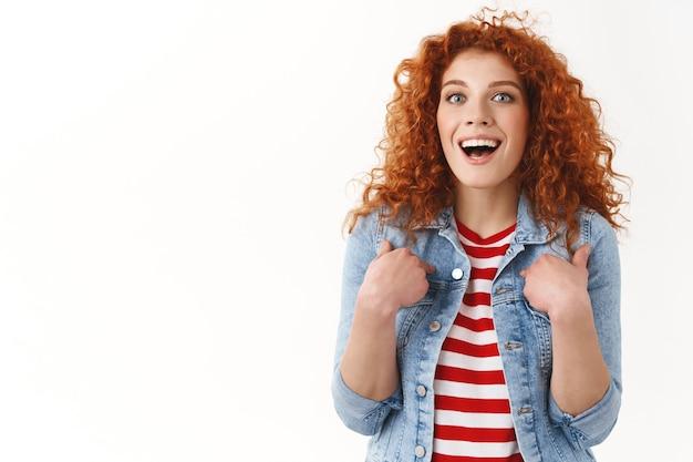 허리 위로 놀란 빨간 머리 세련된 여성 생강 소녀 25대 곱슬머리 자신을 가리키는 깜짝 놀란 자랑 성취 흰색 벽에 서 있는 멋진 기회 달성