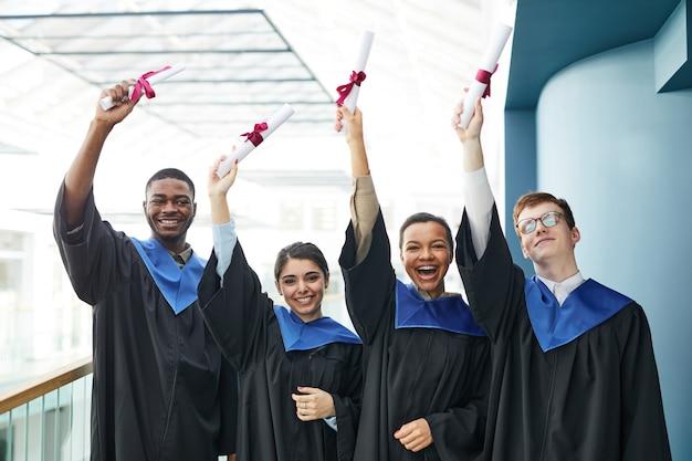 卒業証書を掲げながら、卒業式のガウンを着てカメラに向かって微笑む陽気な若者の多様なグループの腰を上に向ける