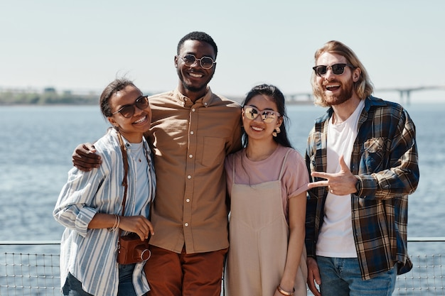 川のそばで屋外でポーズをとっている間、カメラに微笑んでいる若者の多様なグループの腰を上に向けて、すべてサングラスをかけています