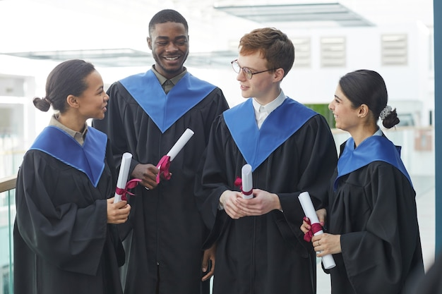 現代の大学のインテリアの屋内で卒業式のガウンを着て、おしゃべりをしている若者の多様なグループの腰を上に向ける