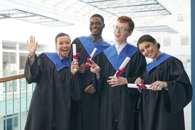 現代の大学のインテリアの屋内で卒業式のガウンを着て、カメラで幸せそうに笑っている若者の多様なグループの腰を上に向ける