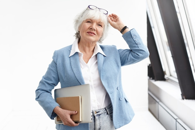 Waist up view of smart classy senior businesswoman wearing stylish blue jacket, jeans and white shirt adjusting glasses on her head, carrying book and laptop, heading to meeting, standing by window