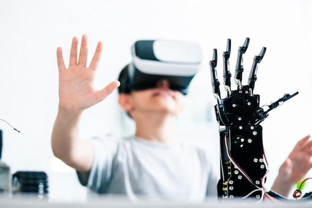 Waist up of a young smart boy wearing vr glasses and controlling his robotic hand
