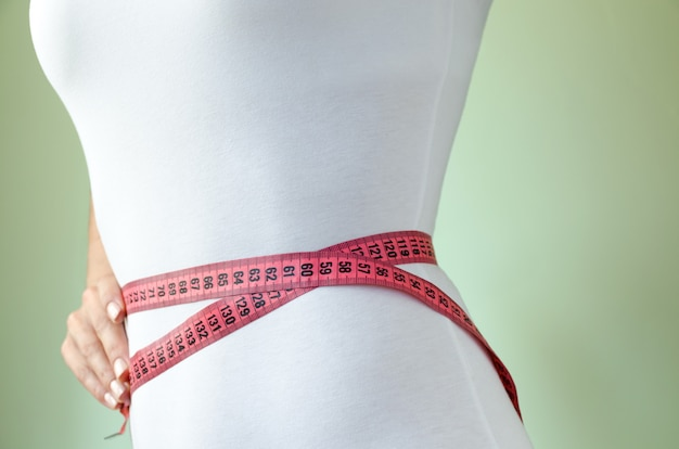 Waist of young, sporty slender girl in white underworld, wrapped in measuring tape. the concept of slimness.