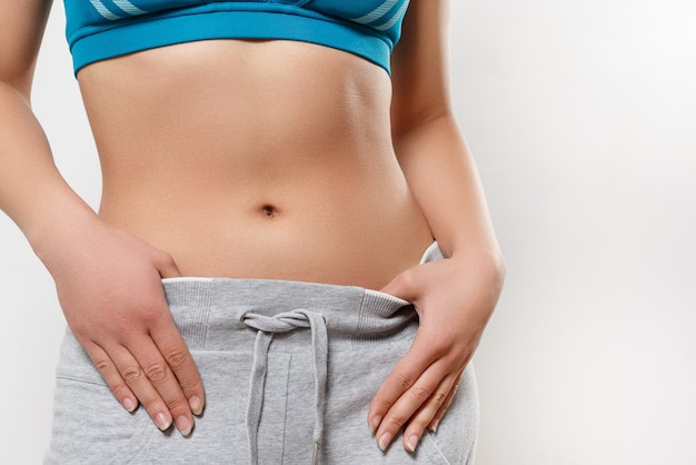 Waist of a young woman in sportswear. on white background