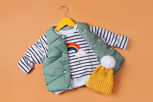 주황색 바탕에 줄무늬 점퍼가 있는 조끼 다운 재킷. 스타일리시한 아동복. 패션 아동복