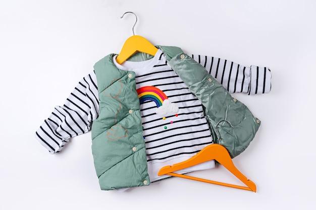 흰색 바탕에 줄무늬 점퍼가 달린 조끼 다운 재킷. 스타일리시한 아동복. 패션 아동복