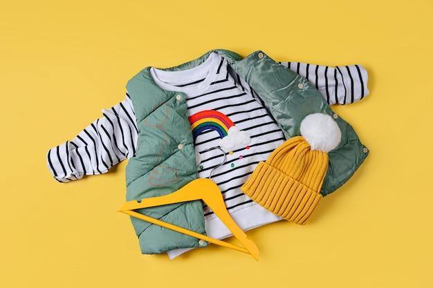 노란색 바탕에 줄무늬 점퍼가 있는 조끼 다운 재킷. 스타일리시한 아동복. 패션 아동복
