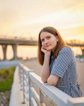 Вертикальный портрет красивой молодой женщины, стоящей на мосту у воды