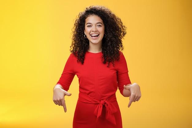 Снимок талии напористой очаровательной и счастливой молодой женщины с кудрявой прической, радостно смеющейся и улыбающейся ...