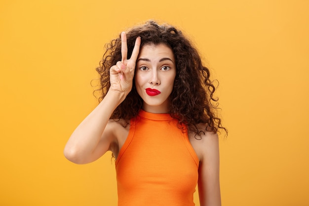 カリスマ的な格好良いヨーロッパの女性のウエストアップショット。クロップドトップに巻き毛のヘアカットが施されています。