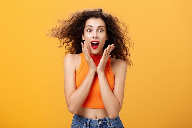 魅力的な熱狂的な魅力的な女性のウエストアップショットは、クロップドトップの巻き毛の髪型で...