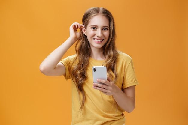 Снимок талии симпатичной и дружелюбной молодой девушки с волнистой прической, прядей волос за ...